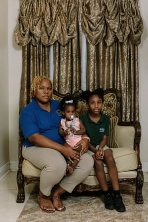 Sheena Dedmond sits at home with her daughters (L to R) Braylein and Baylei. Sheena has lived at the home in Gordon Plaza her entire life.