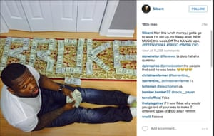 50 Cent posing with wads of bank notes spelling out BROKE