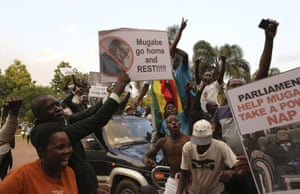 People hold anti-Mugabe placards in Harare