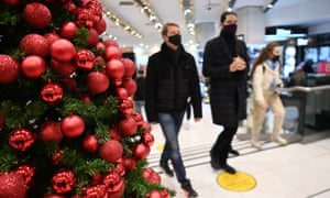 Masked shoppers next to a Christmas tree