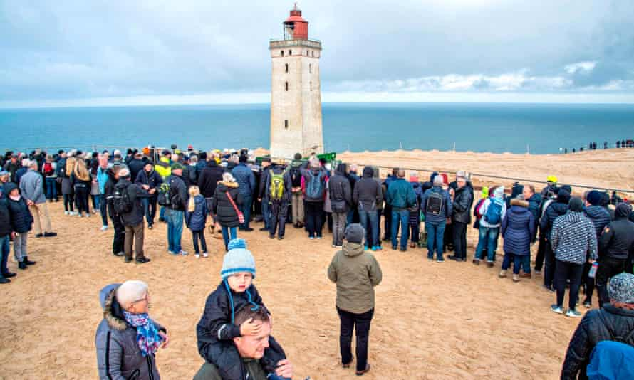 People look on as the lighthouse is moved.