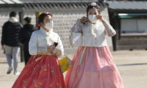 People in traditional Korean hanbok dresses wear face masks as they visit at Gyeongbokgung palace in Seoul on 3 February.