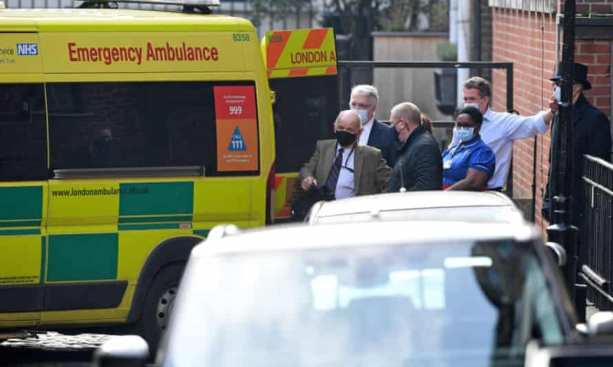 People gather around an ambulance parked outside the rear entrance of King Edward VII's hospital