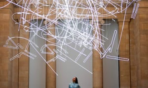 A gallery assistant stands beneath Cerith Wyn Evans's massive new neon installation.