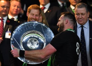 New Zealand's Kieran Read receives the trophy from Prince Harry after the match.