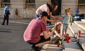 A family lights candles at the entrance of the Romanian Ministry of Interior in Bucharest on Saturday.