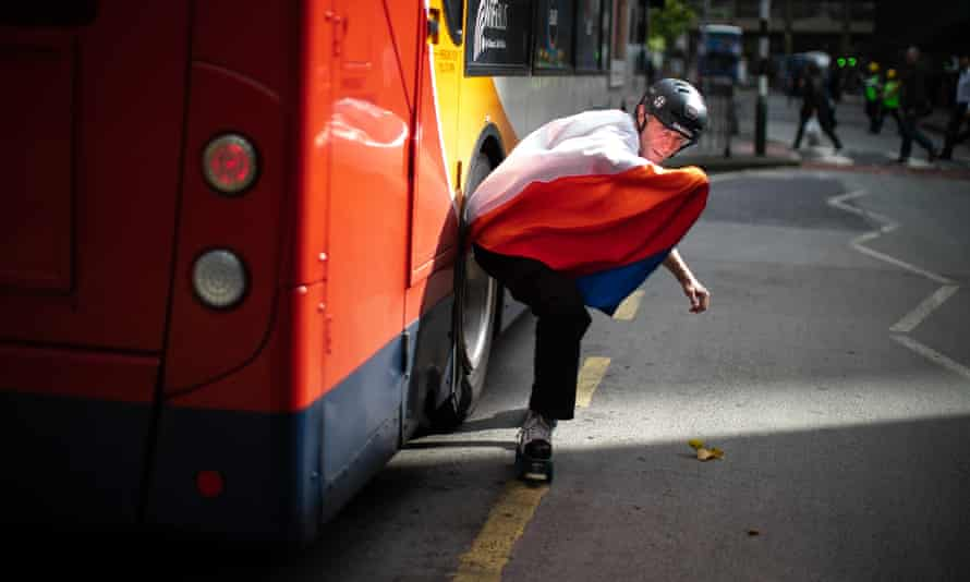 Cast member Steve Long skates past a Stagecoach bus in Manchester