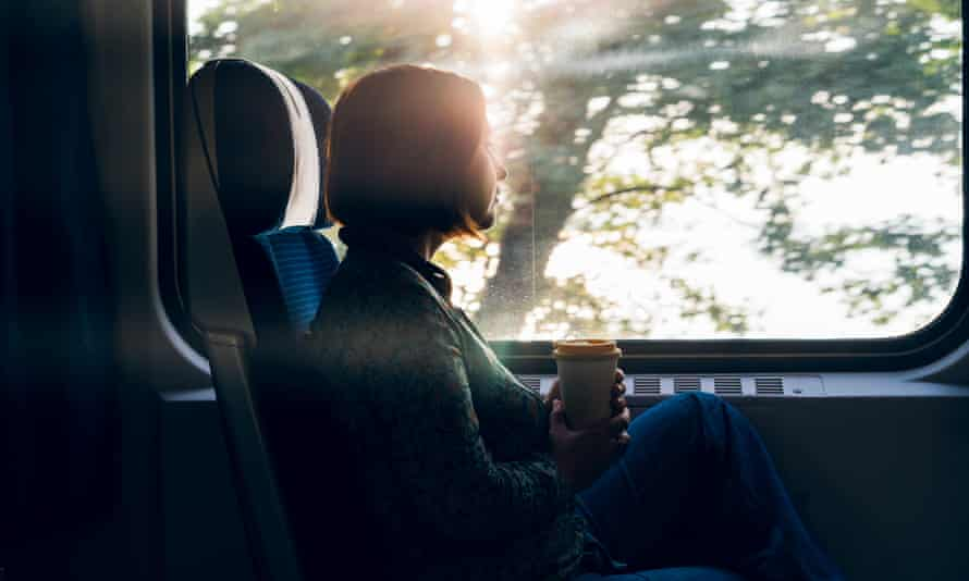 A woman sitting by the window of a commuter train holding a coffee