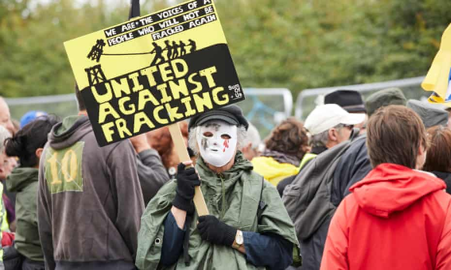 A masked protester holds an anti-fracking sign in Little Plumpton, Lancashire