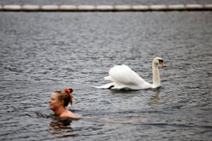 London, UK. A bather swims past a swan in the Serpentine Lido in Hyde Park, as England's third Covid-19 lockdown restrictions ease, allowing outdoor sports facilities to open. England began to further ease its coronavirus lockdown on Monday, spurred by rapid vaccinations, but governments in the rest of Europe struggled to contain Covid-19 surges