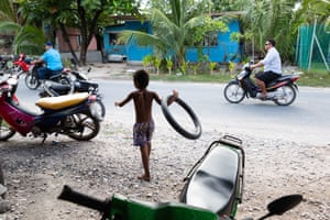 A young boy plays with a bike inner tube in the Tuvaluan capital of Funafuti