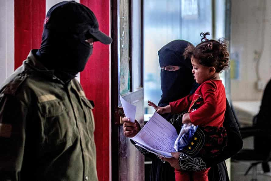 An internal security patrol member looks at a woman holding a baby, reportedly the wife of an Islamic State fighter.