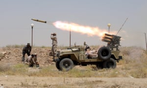 Members of Iraq's Shia paramilitaries launch a rocket towards Islamic State militants in the outskirts of the city of Falluja