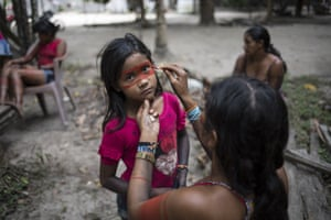 A child stands still as a woman paints a red mask around her eyes, in preparation for a gathering of tribes in the Alto Rio Guama Indigenous Reserve by the Tembe tribes in the village Tekohaw, Para state, Brazil. The indigenous reserve is officially protected, but it's constantly under siege by loggers who illegally try to extract prized hardwood