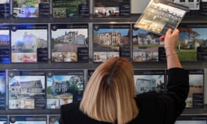 A woman rearranges a display advertising homes