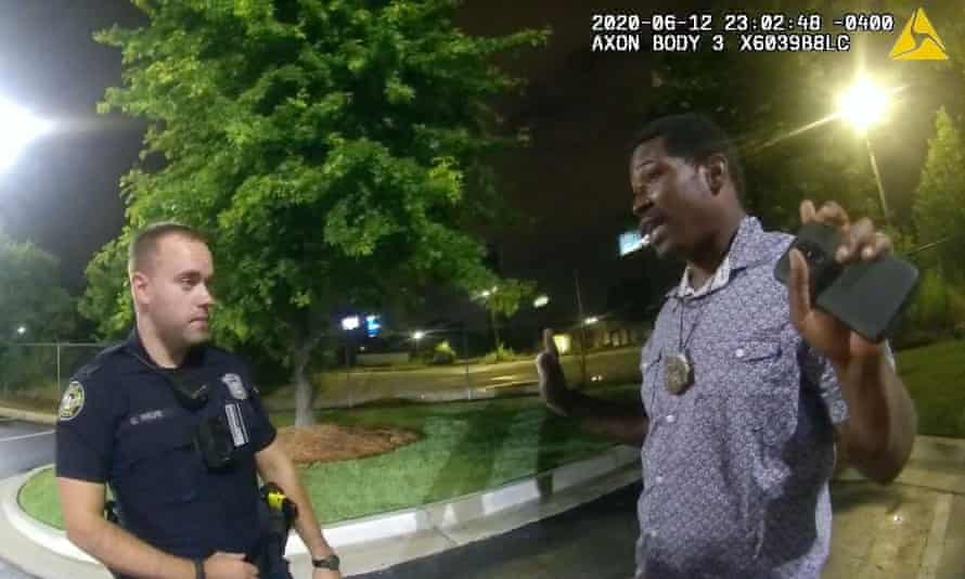 This screengrab taken from body camera video shows Garrett Rolfe with Rayshard Brooks in the moments before Brooks's killing. In the wake of the killing, Rolfe was fired by Atlanta police.