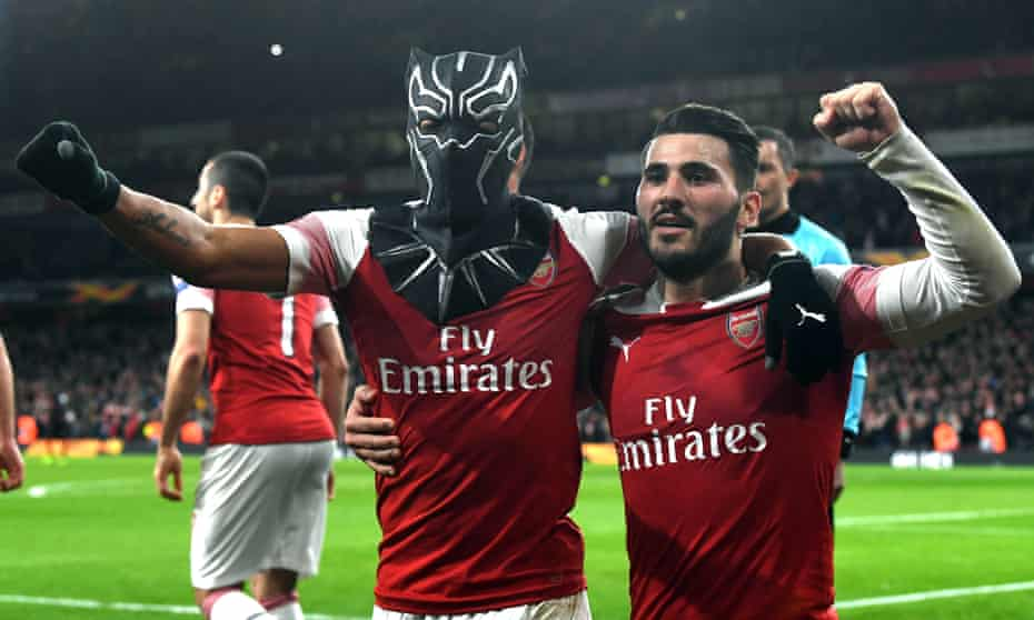 Pierre-Emerick Aubameyang (left) celebrates scoring Arsenal's third goal of the game by wearing a mask in the win against Rennes.