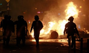 riot police walk near burning objects on the streets