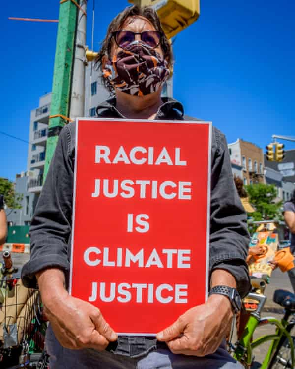 A man holds a sign at a protest in Brooklyn. Some climate activists believe the changes needed to address climate change are in line with the ones that will bring racial justice.