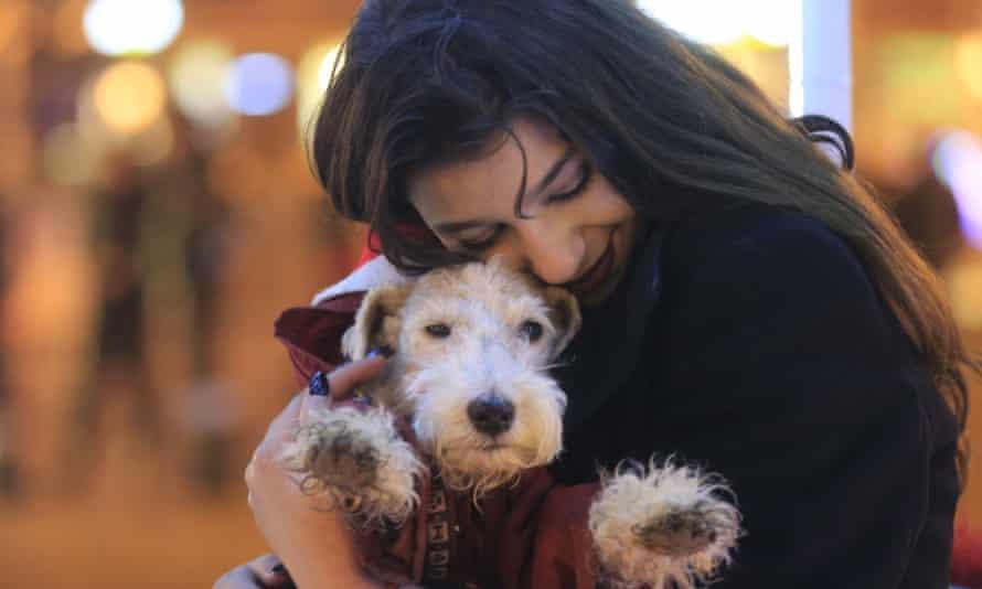 A girl hugs a dog, Ukraine, December 2017.