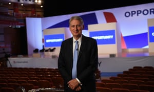 Philip Hammond poses in the conference hall before his speech.