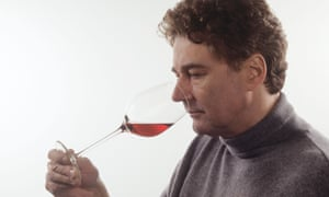 A man smelling a glass of wine