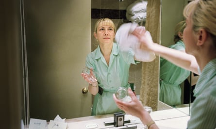 A cleaner polishing a mirror in a London Hotel.
