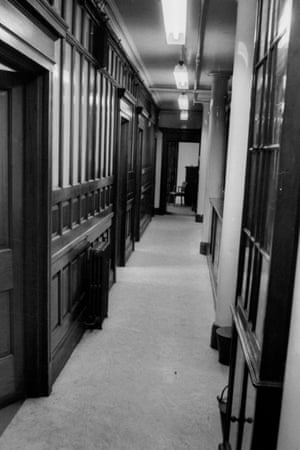 "The editors' corridor in Cross Street. Geoffrey Whatmore, the paper's first professional librarian, described the hallowed aisle in the early 1950s: 'Along the ""corridor,"" the claustrophobic opinion factory tellingly described by Neville Cardus still prevailed. Each leader writer's room had a fireplace and the habit was to litter the room with books and papers, books stacked on chairs, window sills, mantelpiece...For a while the shadowy passage was obstructed by the miscellany editor's large and somnolent dog who would lie across the passageway to the peril of unwary messengers.'"
