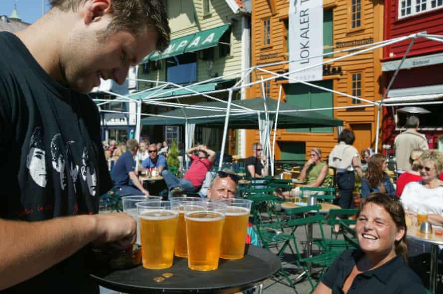 A waiter serves beer outside a bar in Stavanger, Norway