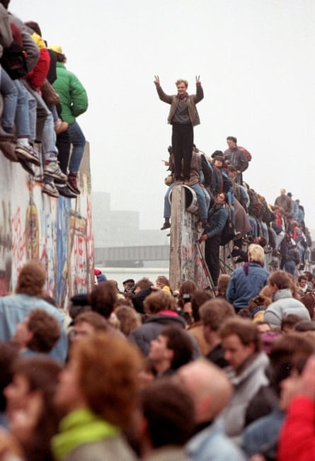 Berliners celebrate on top of the wall as East Germans flood through into West Berlin at Potsdamer Platz.