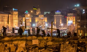 Ukrainian anti-government protesters use snow to reinforce a barricade blocking street access to Independence Square, known as the Euromaidan, in Kiev, in December 2013.