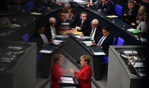Berlin, Germany: Angela Merkel is reflected in a window as she gives a speech