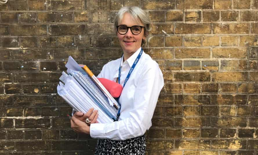 Lucy Kellaway, carrying a pile of marking at school.