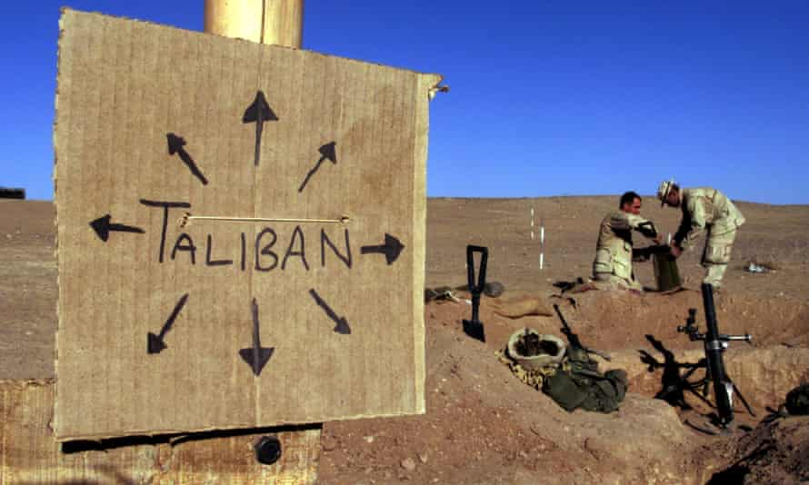 US Marines near a cardboard sign reminding everyone that Taliban forces could be anywhere
