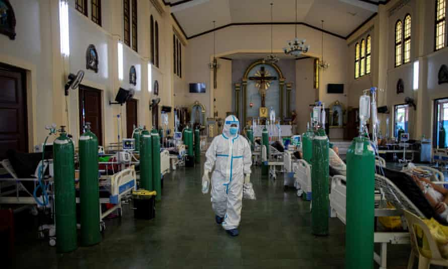 A health worker in the chapel of Quezon city general hospital as the country runs out of staff and facilities.