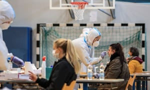 Residents undergo a free rapid antigen nasopharyngeal swab test for Covid-19 at a testing facility set up in a school sports hall today in Bolzano, South Tyrol, Northern Italy, during a three-day mass screening session