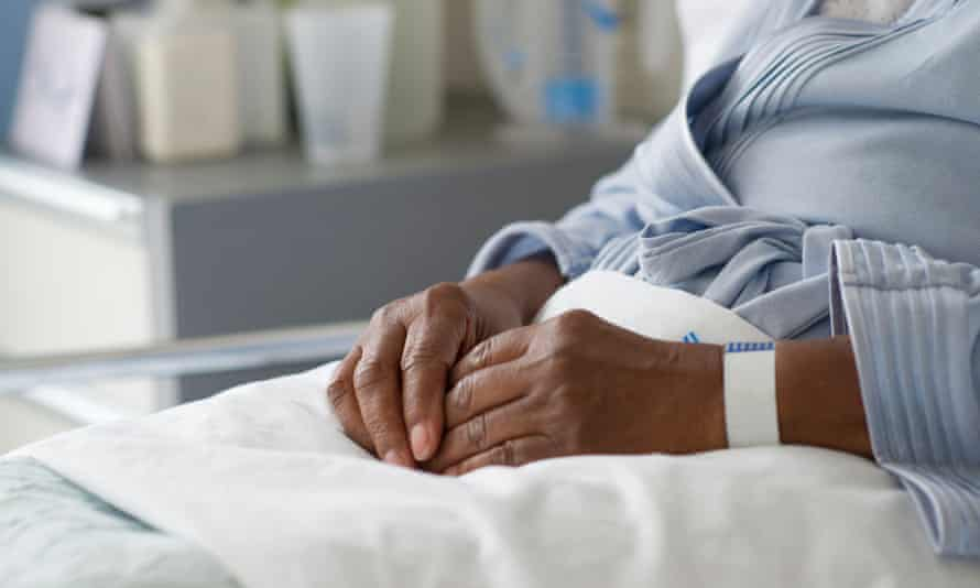 A black woman in hospital receiving treatment