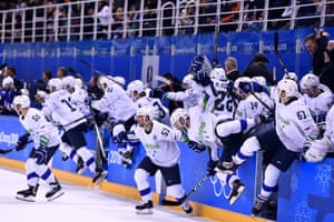 Team Slovenia rushes the ice after the overtime win over the USA.
