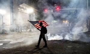A Black Lives Matter protester carries an American flag as teargas fills the air outside the Mark O Hatfield United States courthouse in Portland.