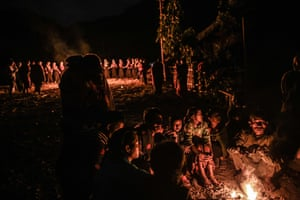 Villagers sit next to a campfire for warmth as Naga tribeswomen continue the ceremony.