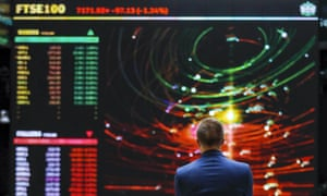 An employee views a FTSE share index board in the atrium of the London Stock Exchange Group Plc's offices in London