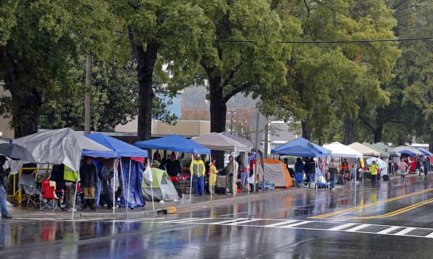 People, some of whom camped overnight, brave the weather as they wait in the rain for the doors to open for a evening campaign rally with President Donald Trump in Charlotte, North Carolina, on Friday.