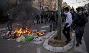 Israeli police officers march by burning rubbish during clashes with ultra-Orthodox Jews in Bnei Brak, Israel