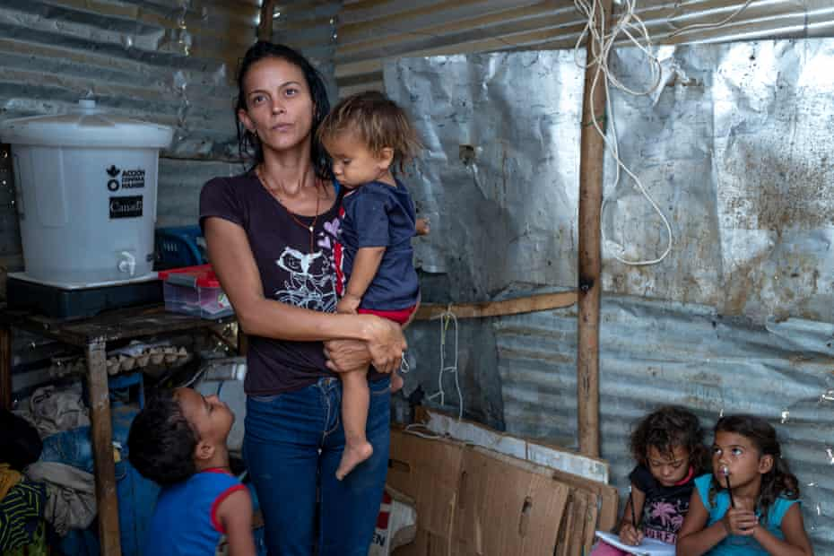 Elaine Rojas, 27, and her four children in the shack in La Pista where they live with her husband and 2,000 other Venezuelan families.