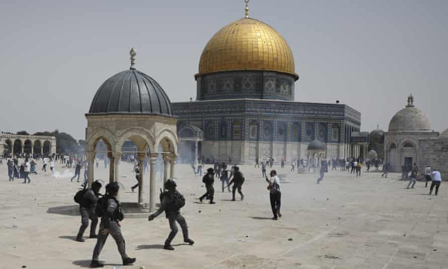 Palestinians run from sound grenades thrown by Israeli police in front of the Dome of the Rock in the al-Aqsa mosque complex in Jerusalem, on 21 May.