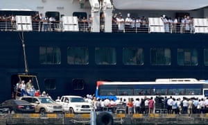 Crew members on the Westerdam cruise ship wave as passengers disembark.