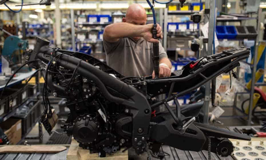 Employees assemble motorcycles on the assembly line at the Triumph Motorcycles factory in Hinckley