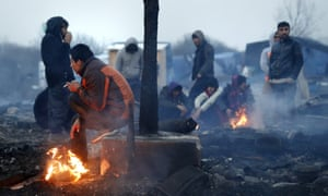 Migrants keep warm during the dismantling of the 'Jungle' makeshift camp in Calais.