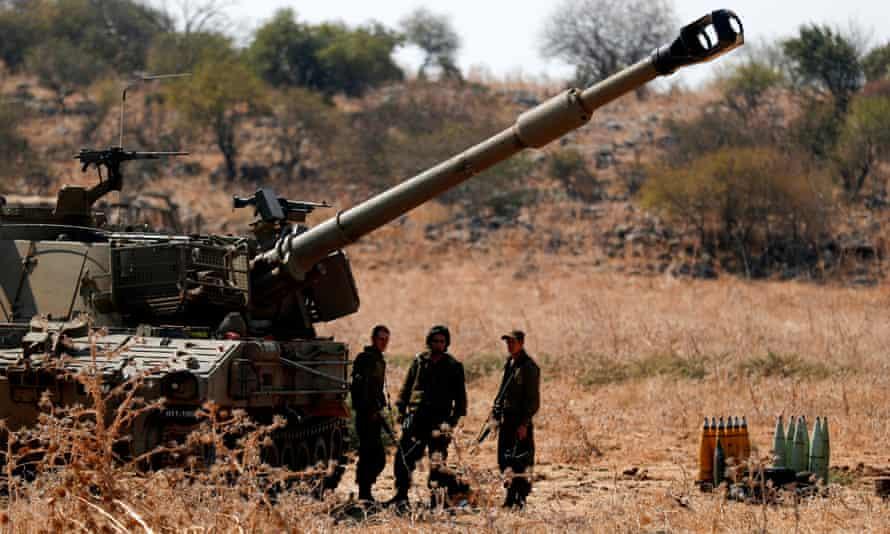 Israeli soldiers stand near artillery units deployed near the Israeli-Lebanon border