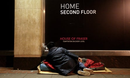 A homeless man rests on his sleeping bag in the street next to a department store.